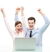 Pareja delante del ordenador portátil con los brazos alzados — Foto de Stock