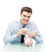 Man putting money in piggy bank — Stock Photo