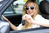 Girl in car holding keys — Stock Photo
