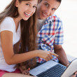 Young couple using laptop outdoors — Stock Photo