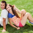 Young couple sitting on grass — Stock Photo