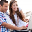 Young couple using laptop — Stock Photo #27036311