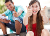 Teenage couple with thumbs up — Stock Photo