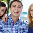 Three young friends standing together — Stock Photo