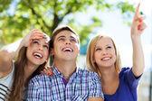 Три молодых друзей указывая — Стоковое фото