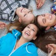 Three young friends lying down — Stock Photo