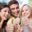 Three young friends with thumbs up — Stock Photo
