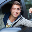 Young man sitting in car holding car keys — Stock Photo #27215639