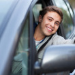 Young man doing thumps-up in car — Stock Photo #27215659