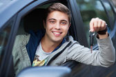 Young man sitting in car holding car keys — Stok fotoğraf