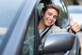 Young man doing thumps-up in car — Stock Photo