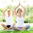 Couple practicing yoga in the park — Stock Photo