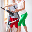 Woman working out while instructor assisting her — Stock Photo
