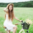Woman riding bicycle in wildflower field — Stock Photo #27258171
