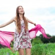 Woman in meadow holding scarf — Stock Photo