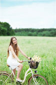 Woman riding bicycle in wildflower field — Stock Photo