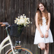 Woman with bike by wooden fence — Stock Photo #27260513