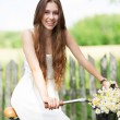 Foto Stock: Woman with bike by wooden fence