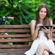 Woman on wooden bench with digital tablet — Stock Photo #27260825