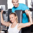 Stock Photo: Trainer helps WomLifting Dumbbells