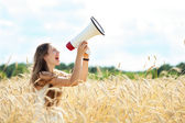 Woman with megaphone in the wheat field — Stock Photo