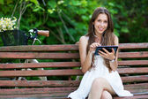 Woman on wooden bench with digital tablet — Stock Photo