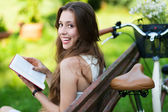 Woman reading book on park bench — Stock Photo