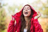 Vrouw in regenjas genieten van de regen — Stockfoto