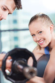 Woman lifting dumbbells while instructor assisting her — Stock Photo