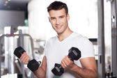 Young man working out at the gym — Stok fotoğraf