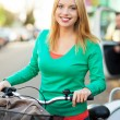 Woman outdoors on bicycle with shopping bags — Stock Photo