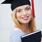 Female graduate holding book — Stock Photo #27293957