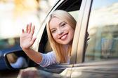 Usmívající se žena sedí v autě — Stock fotografie