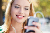 Young woman with music player — Stok fotoğraf
