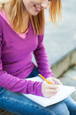 Female student writing in notebook — Foto Stock