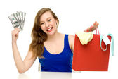 Woman holding shopping bag and money — Stock Photo