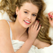 Young woman lying on bed — Stock Photo #27378589