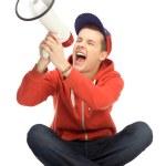 Young man shouting through megaphone — Stock Photo #27379679