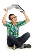Young man holding laptop above head — Stock Photo