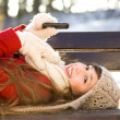 Woman lying on bench with mobile phone — Stock Photo