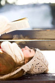Woman reading book outdoors at winter time — Stock Photo