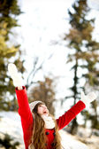 Woman outdoors with arms raised — Stock Photo