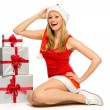 Stock Photo: Woman in Santa hat holding gifts