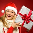 Woman in Santa hat with Christmas present — Stok Fotoğraf #27628151