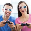 图库照片: Couple in 3d glasses playing video games