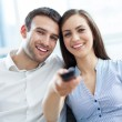 Young couple with TV remote — Stock Photo