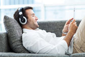 Man on sofa with headphones and digital tablet — Stock Photo