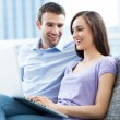 Couple on sofa with laptop — Stock Photo #27660081