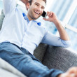 Man on sofa with mobile phone — Stock Photo #27660453