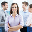 Businesswoman with coworkers in background — Stockfoto